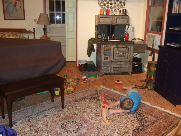 Boy playing with train tracks on the floor. Coal stove sink in thebackground.