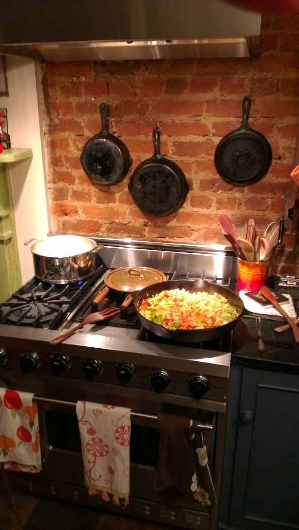 Cast iron pans on bare brick wall above stove cooking dinner